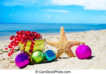 Starfish with gift box and christmas balls on the beach by...
