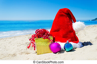 Christmas hat with gift box and christmas balls on the beach...