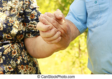 two hands of an elderly couple in love