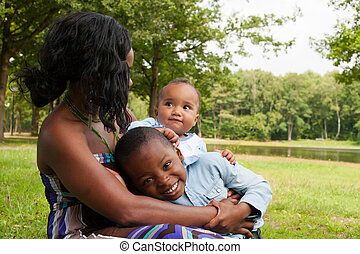 African mother and her children - Happy mixed family is...