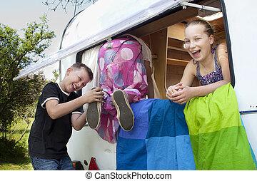 children around an old trailer summer camp holiday fun -...