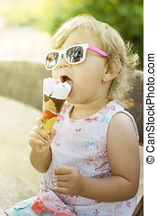 Cute baby girl eating ice cream outdoor