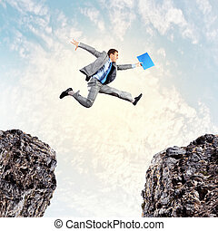 Businessman jumping over gap - Image of young businessman...