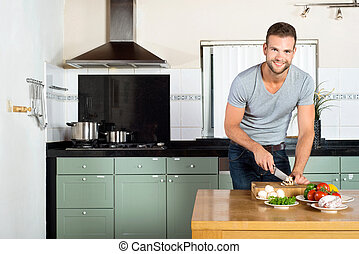 Man Cutting Vegetables At Kitchen Counter - Portrait of...