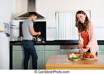 Couple Cooking In Kitchen - Portrait of young woman cutting...
