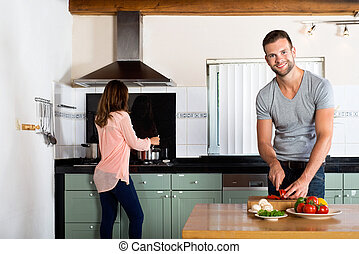 Couple Cooking In Domestic Kitchen - Portrait of young man...