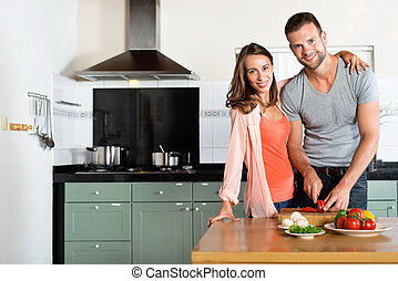 Happy Couple Cutting Vegetables At Kitchen Counter -...