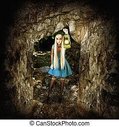 Woman illuminates path in a dark cave - Adventure concept....