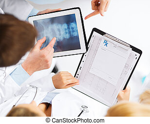 group of doctors looking at x-ray on tablet PC - healthcare,...