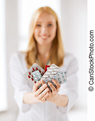 female doctor with packs of pills - healthcare, medical and...