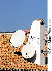 Satellite dishes on chimney, Spain. - Satellite dishes fixed...