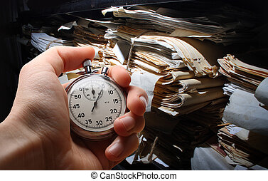 Paper documents stacked in archive - Hand with stopwatch,...