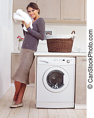 woman on washing machine in kitchen