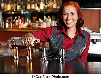 Beautiful redhead barmaid making shots
