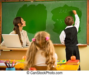 Little schoolboy answering near blackboard in school