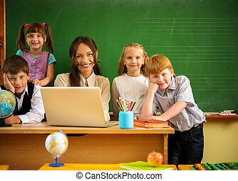 Group of happy classmates with their teacher in class near...