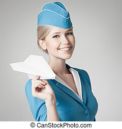 Charming Stewardess Holding Paper Plane In Hand. Gray...
