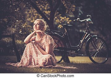 Smiling blond retro woman in summer dress sitting on a...
