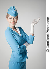 Charming Stewardess Dressed In Blue Uniform Pointing On Gray...
