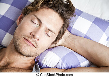 Young man lying in bed sleeping peacefully