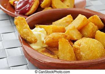 typical spanish patatas bravas, fried potatoes with a hot sauce