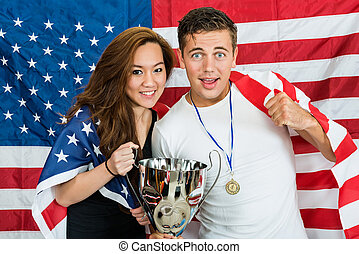 Portrait of happy athletes with trophy and medal standing against North American flag