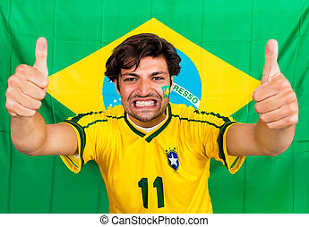 Brazilian sports fan, supporting his national team cheering...