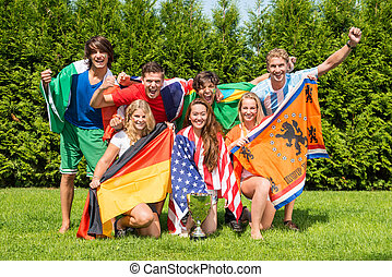 Portrait of cheerful young multiethnic athletes with various...