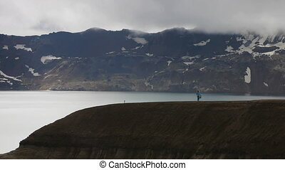 woman walking on a crater rim - tourist walks on a edge of...