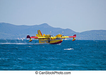 Firefighting airplane taking water from sea - Firefighting...