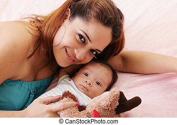 Happy mum and baby boy smiling in the bed holding teddy bear