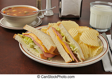 Soup and sandwich - A bologna and cheese sandwich with...