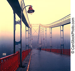 Old pedestrian bridge in Kiev in the early morning mist, the...
