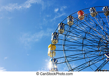 ferry wheel under bright blue sky