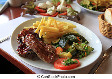 T-Bone Steak - Dinner plate with t-bone steak, potato and...