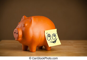 Post-it note with smiley face sticked on piggy bank - Drawn...