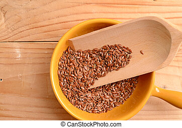 Flaxseed in a ceramic bowl on a wooden table