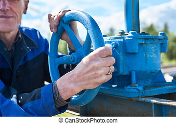 Hands close-up of senior manual worker turning cut-off valve at plant