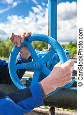 Hands close-up of mature manual worker turning stop-gate valve