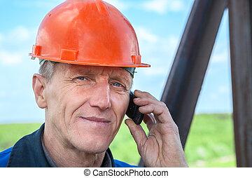 Senior manual worker in orange hardhat calling on the phone