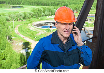 Senior man in orange hardhat calling on the phone