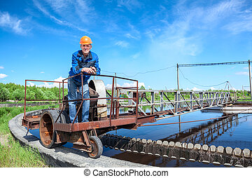 Senior worker standing on waste water treatment unit on...