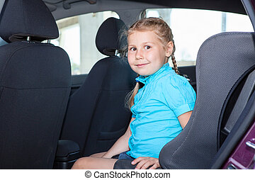 Young girl sitting in car safety seat on back of vehicle