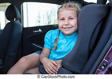 Happy smiling young girl sitting in infant restraint seat in...