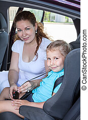Small child in car safty seat with helping mother Caucasian...