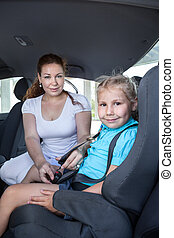 Mother helping daughter to fasten car safety belt in...