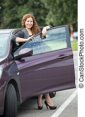 Laughing girl with curly hair standing near your new car...