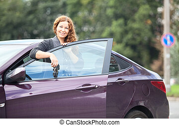 Caucasian brunett young woman near own car with keys