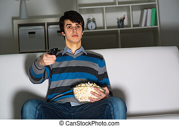 young man watching television with popcorn, remote control...