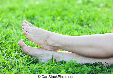 Barefooted attractive female feet on green grass vertical...